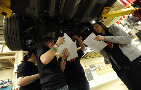 Female students from Brewer High School and Old Town High School try to identify automotive components from under a car at United Technologies Center in Bangor on Friday, April 6, 2012 during the 10th annual Totally Trades! conference.