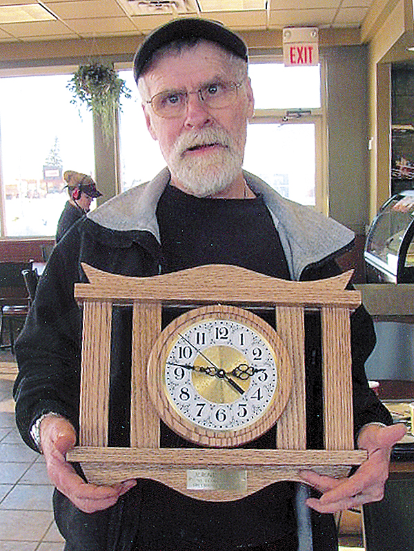 Jerome Hogan holds the mantel clock that a friend, Jim Clark, made to celebrate Hogan's 50 years of service at the Greyhound terminal on Main Street in Bangor.