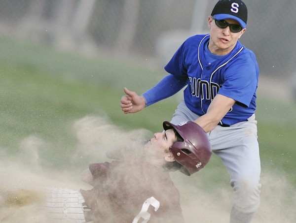 Sumner Tiger shortstop Dillon Harmon (6) delivers a tag to the chin of George Stevens Academy's Ben Eley in the second inning of their game in Blue Hill on Tuesday, April 17, 2012.