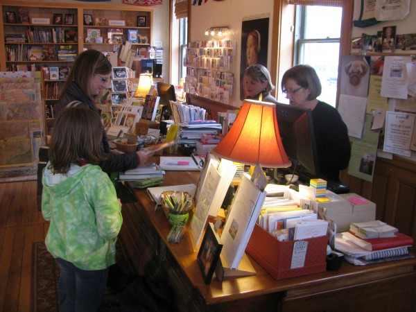 Gretchen Warsen of Nashua, N.H. makes a purchase at Left Bank Books Friday morning with her daughters Meredith, 9, and Millie, 6. Bookstore owners Lindsay McGuire (left) and Barbara Klausmeyer stand behind the counter of the crowded store, which will move to a new space on Church Street in Belfast in mid to late June.