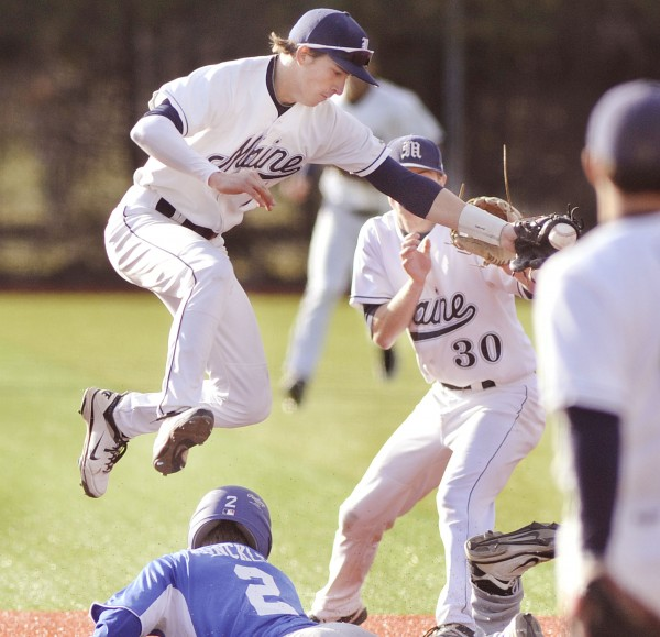 UMaine baseball shortstop Mike Fronsoso hangs onto the ball as he leaps over a diving Colby player Luke Dunklee (2) at second base in the fourth inning of their game in Orono on Tuesday, April 10, 2012.