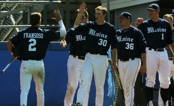 UMaine's Michael Fransoso (left) gets high-fives from his teammates after scoring in the sixth inning against Hartford at the Orono campus of the University of Maine on Sunday, April 15, 2012.
