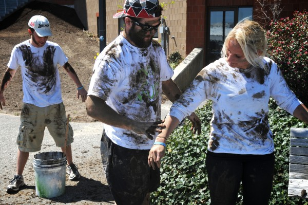 USM students Austin Brown (from left), Dan Rautenberg and Katie Paradis slather themselves with mud on the Portland campus before heading into downtown Thursday, April 19, 2012 to promote the Into the Mud Challenge. The challenge is a 2.5 mile muddy footrace in Gorham May 5 to raise money for the USM Sports Management Scholarship Fund.