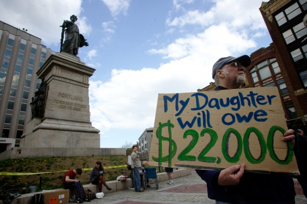 Val Hart holds a sign in Portland's Monument Square on Wednesday, April 25, 2012 during an Occupy movement's protest of the student loan crisis. Hart says his daughter will bear over $22,000 in student loans even after he chips in and she receives scholarships.