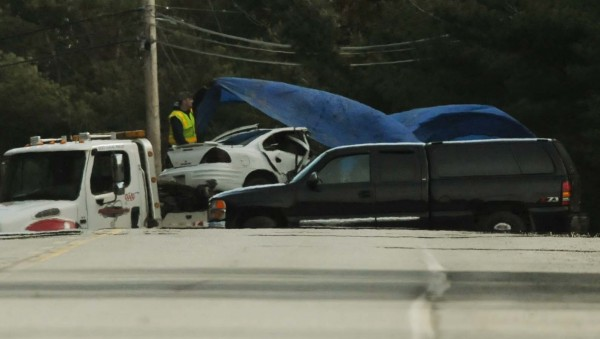 A wrecker driver covers a car that was involved in a fatal accident on South Main Street in Old Town on Tuesday, April 10, 2012.