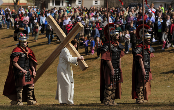 Tim Mullen (center), dressed as Jesus and surrounded by Roman soliders, walks to the 5th Station of the cross at Indian Trail Park in Brewer, on Sunday, April 1, 2012, where Simon of Cyrene joins him to help him carry the cross.