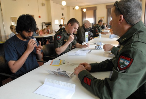 University of Maine graduate student Praveen Gunturi (left) and game warden Evan Franklin swab their mouths at the stem cell drive hosted by the University of Maine football team at the Memorial Union on Wednesday. Many game wardens turned out to give samples in hopes of being a donor for their deputy chief Gregory Sanborn, who has cancer. At far right is game warden Joe Gardner, who was instructing donors on the proper way to swab.