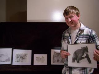 Tyler Durling of Wesley displays several of his drawing (from left) of an eagle, moose, dog, wolf and, in hand, a bear with a salmon in its mouth, which won first place in a Downeast Salmon Federation student art contest.