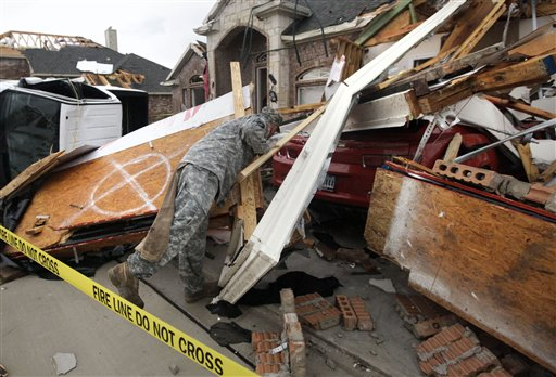 Texas Army National Guard Cpl. Brock Fischer of Charlie Troop, 3-124 Cav., searches a vehicle in front of a tornado damaged home Tuesday, April 3, 2012, in Forney, Texas.