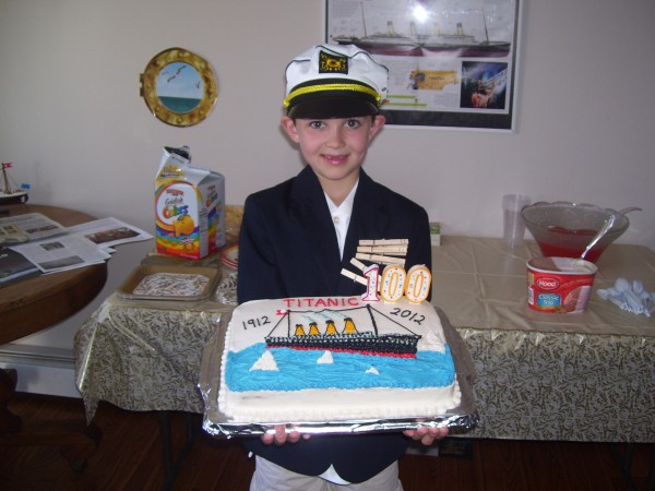 Nathan Carey, 8, dressed as the Titanic's Capt. Edward John Smith, holds a Titanic 100th anniversary cake at the party he arranged to commemorate the sinking of the great ship.