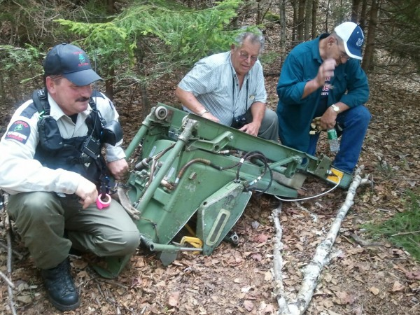 Sgt. Bruce Reed of the Maine Forest Service, Pete Pratt of the Moosehead Riders Snowmobile Club and club member Dave Demers examine the B-52 ejection seat Reed found while hunting last fall after a hike on Elephant Mountain on May 24, 2012.