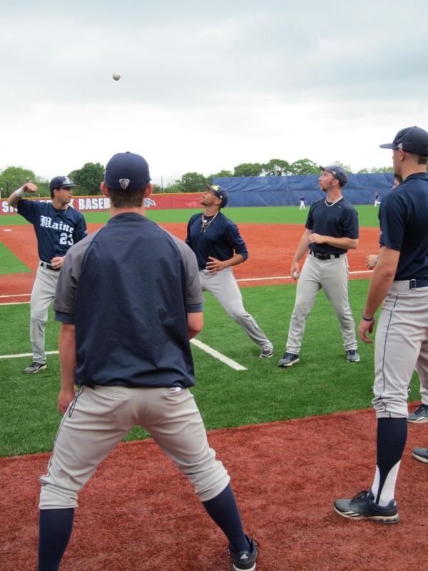 Members of the UMaine baseball team engage in a game of &quot2 Ball&quot during warmups for Thursday's game against Albany at the America East tournament in Stony Brook, N.Y. The Black Bears won 8-3.