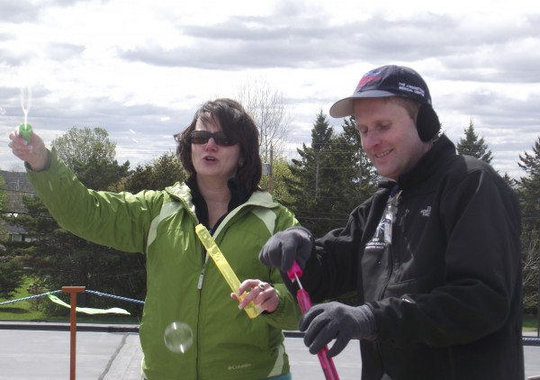 Jason Parent (right), director of advancement for The Aroostook Medical Center, and Lisa Miles, general manager for Cumulus Broadcasting in Presque Isle, blow bubbles on top of the roof at The Aroostook Medical Center on Thursday, May 17, 2012, to try and attract the attention of passersby. The two began camping out on the roof Thursday morning and will remain there until 9 a.m. Friday to raise money for Cancer Care Services at TAMC and the Aroostook County Relay For Life