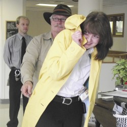 "Laura Turner, manager of social services at The Aroostook Medical Center in Presque Isle, tries to hide after she was ""arrested"" Thursday, May 17, 2012, as part of the Rally On The Roof fundraiser. For $150, a donor could secure a ""warrant"" to have someone detained and taken up to the hospital roof. It is then up to the detainee to raise an average of $300 bail by calling friends, family members and others to pledge the money to secure their release."