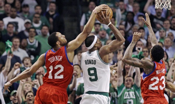 Philadelphia 76ers shooting guard Evan Turner (12) reaches over the top to block a shot by Boston Celtics point guard Rajon Rondo (9) during the second half of Game 2 in their NBA basketball Eastern Conference semifinal playoff series in Boston, Monday, May 14, 2012. The 76ers won 82-81.