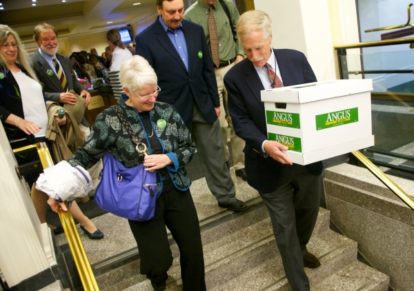 Former governor and U.S. Senate hopeful Angus King carries a box of signature-filled petitions to the Cross Building in Augusta Tuesday, May 29, 2012