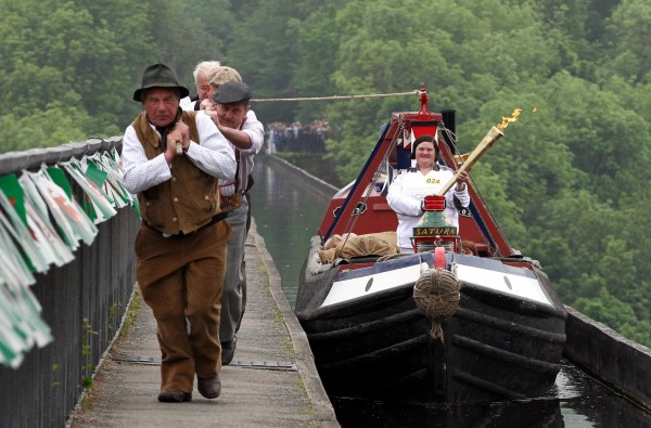 This image released by LOCOG shows Joanne Gregory travelling across the Pontcysyllte Aqueduct with the Olympic Flame during the Torch Relay leg between Wrexham and Trevor on Wednesday, May 30, 2012.