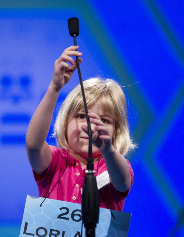 Six-year-old Lori Anne Madison, of Woodbridge, Va., the youngest contestant in the history of the National Spelling Bee, reaches for the microphone during the second round on Wednesday, May 30, 2012, in Oxon Hill, Md.