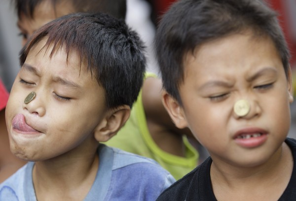 Filipino boys use their faces to move a coin close to their mouth during a game as part of celebrations of the feast day of Saint Rita de Cascia in suburban Paranaque, south of Manila, Philippines on Sunday May 20, 2012. Philippine fiestas, a festive time for family and friendly reunions, are held in towns nationwide traditionally during the hot summer months to venerate patron saints and for thanksgiving in this predominantly Roman Catholic nation.