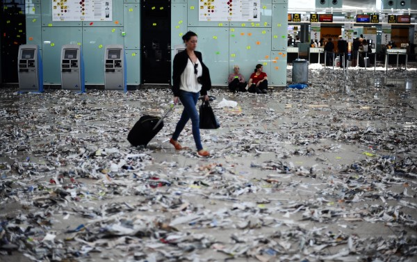 A passenger walk among rubbish and paper during a strike by the cleaning staff against budget cuts at Barcelona's airport in Barcelona, Spain on Wednesday, May 30, 2012.