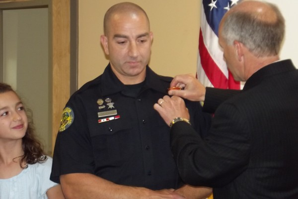 Bangor Police Chief Ron Gastia (right) pins a sergeant badge to the uniform of now-Sgt. Rob Angelo (center) during a promotion ceremony Wednesday at the police department. Angelo's 9-year-old daughter Isabelle (left) and wife Laura attended the afternoon ceremony along with Bangor law enforcement and other police department staff.