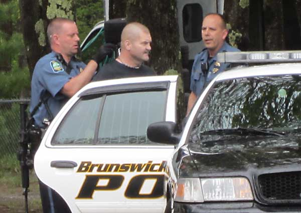 "Brunswick Police Lt. Tom Garrepy, left, and Sgt. Russ Wrede place Charles ""Muggy"" McKenney Jr. in a cruiser Wednesday following his arrest on two counts of Class A felony aggravated trafficking in scheduled drugs."
