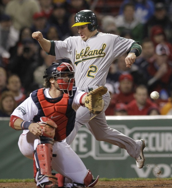 Oakland Athletics' Cliff Pennington (2) beats the throw into Boston Red Sox catcher Jarrod Saltalamacchia to score on a single by Jemile Weeks during the fourth inning of a baseball game at Fenway Park in Boston, Tuesday, May 1, 2012.
