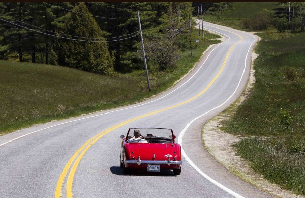 The open road calls as Jim Begin cruises down Pleasant Hill Road in his restored 1962 Austin Healey 3000 Tri-Carb Roadster in Brunswick, Saturday, May 19.