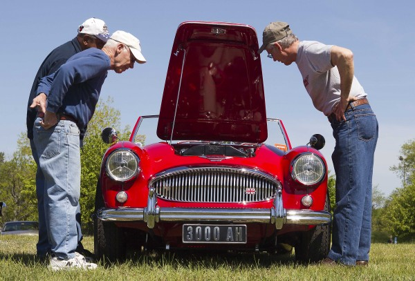 Jim Begin (right) and visitors to a car show are careful not to touch the paint as they peer into the engine compartment of Begin's 1962 Austin Healey in Brunswick, Saturday, May 19. Begin took first place in the import class at the show.