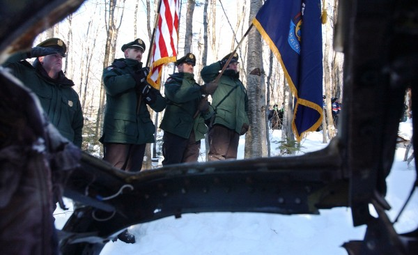 Members of the Maine State Warden Service color guard (from left) Warden Adam Gormley, Sgt. Greg Sanborn, Warden Ron Dunham and Sgt. Dan Menard stand at attention at the site of the1963, B-52 crash at Elephant Mountain in Greenville during a flyover by three helicopters from the 101st Army National Guard in Bangor in January 2003.