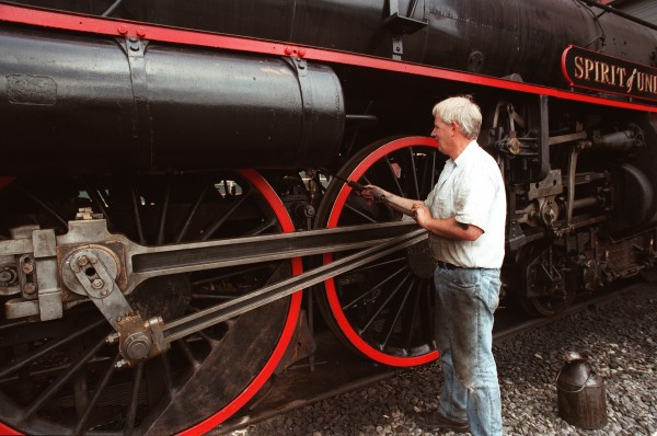 Bill Alexander of Albion, a fireman on the Belfast & Moosehead Railroad, lubricates the wheels of a 1913 Swedish steam locomotive at the railyard in Unity in April 2006.