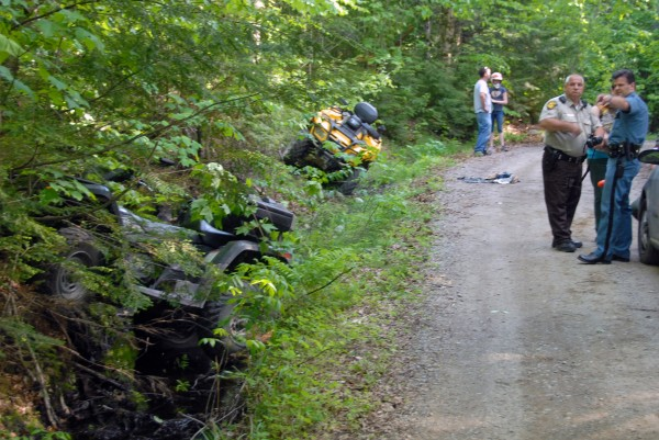 Maine state Trooper Thomas Fiske (farthest right) explains an ATV accident to Penobscot County Sheriff's Deputy Mike Knights on a road off Madagascal Pond in Burlington on Saturday, May 26, 2012.