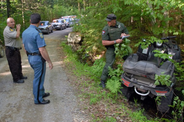 Penobscot County Sheriff's Deputy Mike Knights (left) discusses with Maine state Trooper Thomas Fiske (center) and Maine Game Warden Bruce Loring an ATV accident on a road off Madagascal Pond in Burlington on Saturday, May 26, 2012.