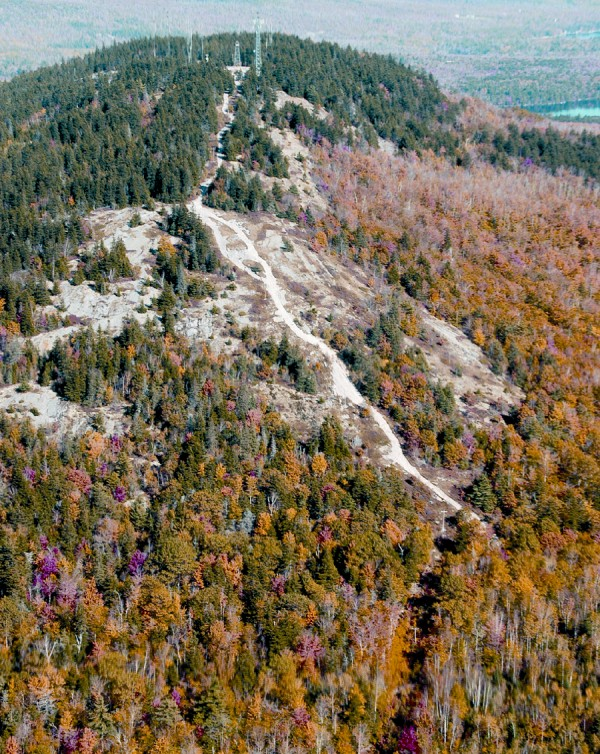Along the southwestern slope of Bald Mountain in Dedham, a white slash marks the trail used by hikers and service vehicles to reach the summit and its nine communications towers. The open areas along the mountainside once were ski trails created for the Bald Mountain Ski Area.