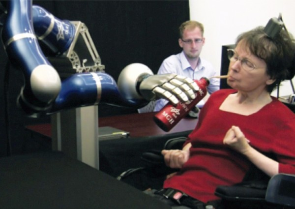 In this April 12, 2011 image from video provided by braingate2.org, Cathy Hutchinson of East Taunton, Mass., sips a drink held by a robotic arm during a test at a long-term care residence for adults with neurological disease in Dorchester, Mass. A report by researchers published in the Thursday, May 17, 2012 issue of the journal Nature describes how two people, paralyzed years before by strokes, were able to control free-standing robotic arms with the help of a tiny sensor planted in their brains. The sensor, about the size of a baby aspirin, eavesdropped on the electrical activity of a few dozen brain cells as the people imagined moving their arms. It then sent signals to a computer, which translated them into commands for the robot arms.