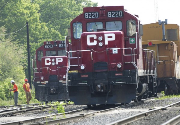 Surveyors work next to Canadian Pacific Rail trains which are parked on the train tracks in Toronto on Wednesday, May 23, 2012. Canada's labor minister said Wednesday the government will introduce legislation if necessary to end a strike at Canadian Pacific railway, which has forced the suspension of its freight service in Canada and the United States.