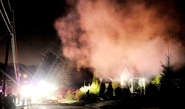 Lights from the Auburn Fire Department light up Paul Street as a fire burns at a single-family home Tuesday night. While Auburn and Mechanic Falls battled the blaze, Lewiston firefighters responded to a fire on Spring Street in Lewiston.