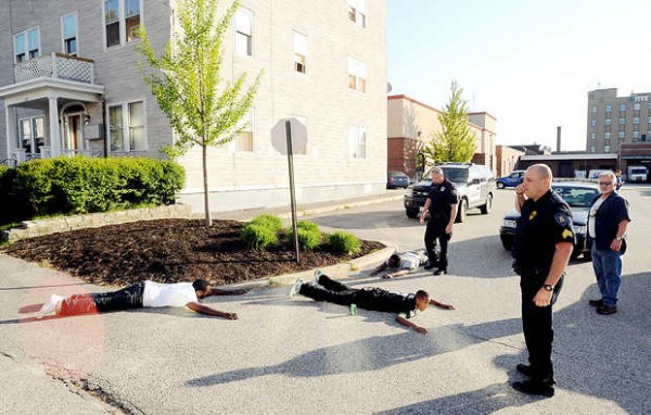 Police officers have three men on the ground near the corner of Bates and Ash Streets in Lewiston on Friday evening.