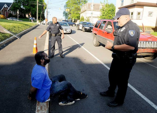 Lewiston police officers question a man in hand cuffs on Ash Street in Lewiston on Friday evening.