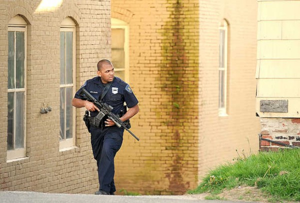 Lewiston police Officer Joseph Philippon covers 111 Blake St. in Lewiston on Friday evening.