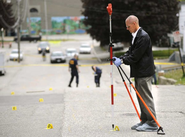 Detective Terry James of the Maine State Police marks the coordinates of the blood stains at the scene of a stabbing on Howe Street in Lewiston on Sunday.