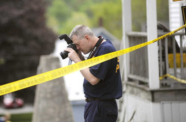 Herb Leighton of the Maine State Police photographs the scene of a stabbing on Howe Street in Lewiston on Sunday.