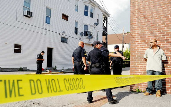 A Lewiston police officer asks a man to stand behind the crime scene tape at the corner of Granite and Bates Streets in Lewiston on Wednesday. A bleeding man collapsed in the doorway of the tenement building in the background.