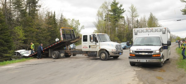 An ambulance leaves the scene of a two-car crash as a wrecker pulls one of the vehicles from the ditch at the intersection of Route 15 and Route 43 in Corinth on Friday afternoon, May 11, 2012.