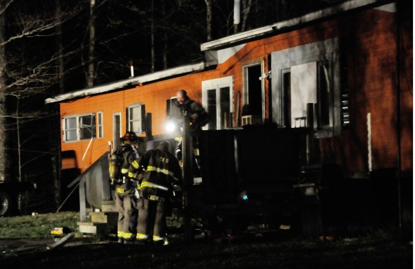 Firefighters look over debris on the front porch after dousing a fire that broke out in a living room of a trailer home on Penny Lane in Carmel just before 9 p.m. Monday, May 7, 2012. The inhabitant made it out safety but was treated briefly in a Carmel ambulance.