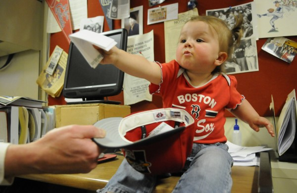 Chloe Thibodeau picks school names out of a Portland Sea Dogs hat as part of a BDN game-reporting contest at the Bangor Daily News Tuesday. Chloe, who is 15 months old, selected the Old Town softball and Orono baseball teams as the two teams awarded 25 tickets each to a Sea Dogs game on May 28 in Portland.