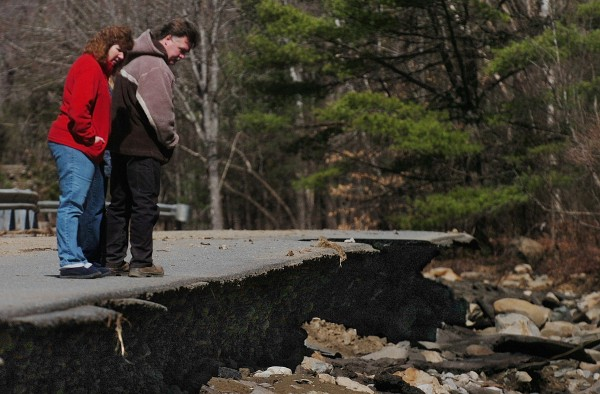 During a Saturday afternoon stroll, Kelly and Leon Licata of Orrington, who live on the nearby Blake Road, look over the newly formed precipice on the Swetts Pond Road created by a dam breach in Orrington on Friday, March 23, 2012.