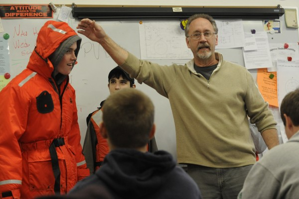 Deer Isle-Stonington High School marine trades instructor Tom Duym has student freshman Josh Gove,15 of Deer Isle try on a flotation jacket as freshman Tyler Wheaton 15, of Stonington and other students look on in 2010.