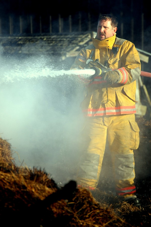 Jeff Alley Jr., chief of the Winter Harbor Fire Department, works a hose outside the old wooden barn that was the centerpiece of the Darthia Farm on West Bay Road in Gouldsboro where an early Monday fire destroyed the barn and killed horses, sheep, pigs, calves and chicks that were inside.