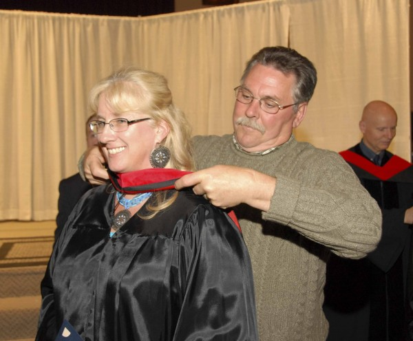During the Grace Evangelical College and Seminary commencement held at Bangor Baptist Church on May 9, 2012, David H. Stevens of Bangor places a master's hood on his wife, Charyl Chandler-Stevens. She earned her master of arts in biblical studies.